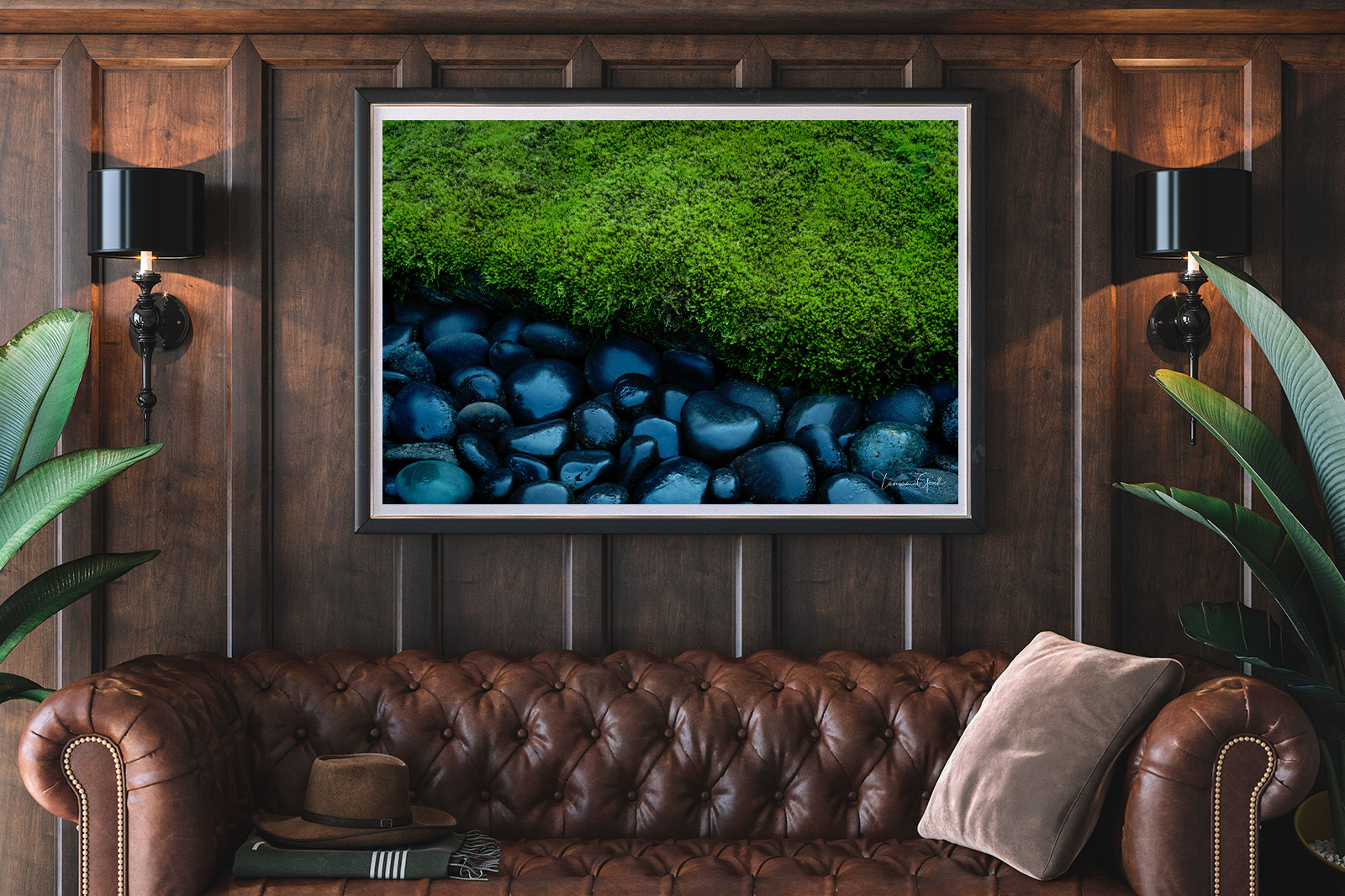A framed print of Moss and rocks hanging over a leather couch.